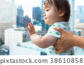 Toddler boy looking out at the city a glass 38610858