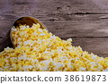 Box of popcorn spilled on wood background. 38619873