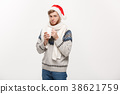 Christmas concept - Young beard man in sweater and 38621759