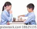 Boy makes the first chess move. 38625135