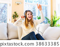 Happy young woman listening to music on headphones 38633385