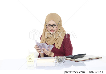 sitting on workplace and holding banknote 38637041