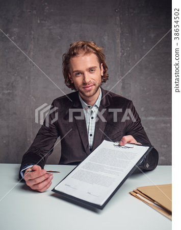 Happy male demonstrating contract at table 38654502