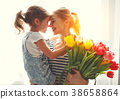happy mother's day! child daughter   gives mother a bouquet of f 38658864
