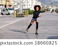 Black woman on roller skates riding outdoors on urban street 38660825