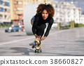 Black woman on roller skates riding outdoors on urban street 38660827