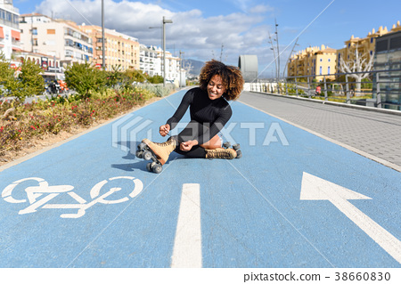Young smiling black girl sitting on bike line and puts on skates 38660830