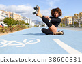 Funny smiling black girl sitting on bike line and puts on skates 38660831