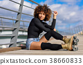 Afro hairstyle woman on roller skates sitting on urban bridge 38660833