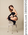 blond woman sitting squatting back on white chair 38660956