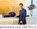 Hotel receptionist check in man giving key card 38670112