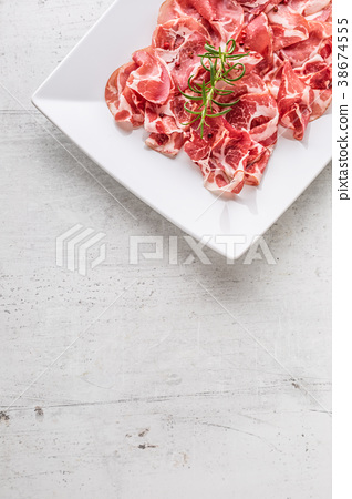 Curled slices of delicious prosciutto with herb. 38674555