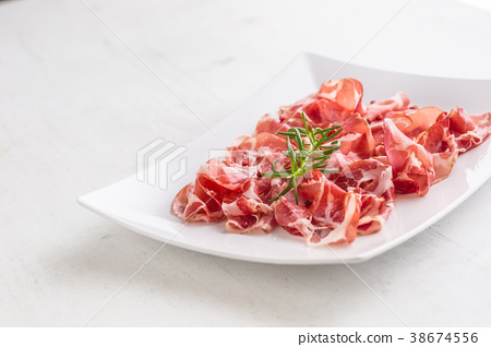 Curled slices of delicious prosciutto with herb. 38674556