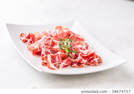 Curled slices of delicious prosciutto with herb. 38674557