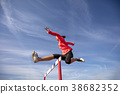 Female athlete jumping above the hurdle during the 38682352