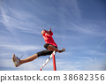 Female athlete jumping above the hurdle during the 38682356