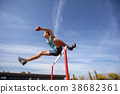 Low angle view of determined male athlete jumping 38682361
