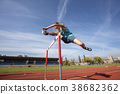 Low angle view of determined male athlete jumping 38682362