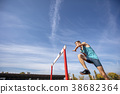 Low angle view of determined male athlete jumping 38682364