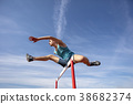 Low angle view of determined male athlete jumping 38682374