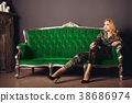 Beautiful young woman  sits on green vintage couch 38686974