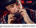 The musician plays on the harmonica. 38691683