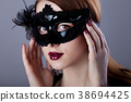 Young redhead woman in carnival mask 38694425