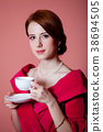 woman in red Victorian epoch clothes with cup  38694505