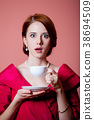 woman in red Victorian epoch clothes with cup 38694509
