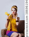 girl in 70s clothes style sitting in armchair 38696194