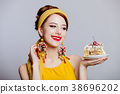 girl in 70s clothes style with cake 38696202