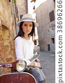Young beautiful woman sitting on a italian scooter. 38696266