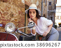 Young beautiful woman sitting on a italian scooter. 38696267