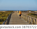 People running in a dune walkway near the sea at 38703722