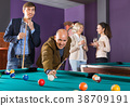 Group of cheerful friends playing billiards 38709191