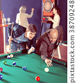 Group of friends playing billiards 38709248