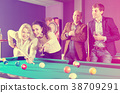 Group of friends playing billiards 38709291