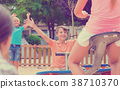 Cheerful children are teetering on the swing 38710370