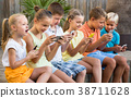 Group of glad children playing with mobile phones outdoors 38711628