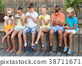children in school age looking at mobile phones and sitting outdoors 38711671