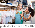 young woman and girl in clothes store. 38712107