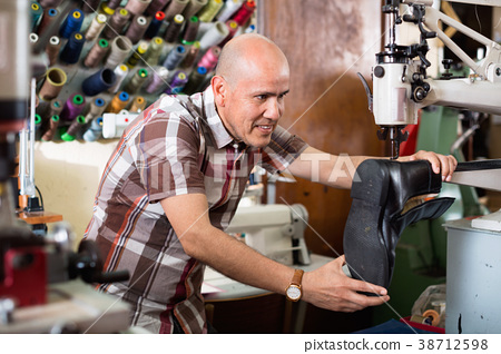 Mature diligent workman sewing leather boots on stitch lathe 38712598