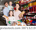 parents with two kids choosing biscuits in store 38713219