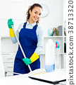 Woman with supplies cleaning in office 38713320