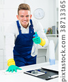 Handsome guy in uniform cleaning in office 38713365