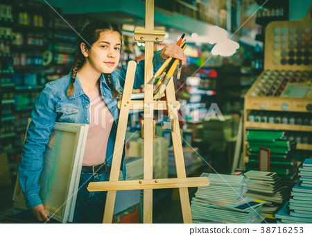 Teen girl holding supplies for painting in hands in art department 38716253