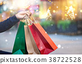 Shopping bags in hand with snowflake on christmas 38722528