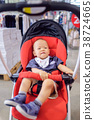 Toddler boy sitting on stroller shopping in store 38724665