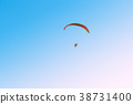 paramotor flying on blue sky and light of the sun. 38731400