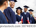 happy students in mortar boards with diplomas 38746939